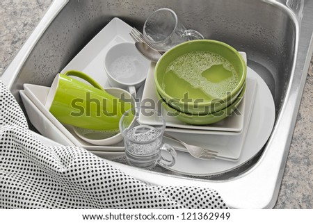 Dishwashing. Bright dishes in the sink and kitchen towel.