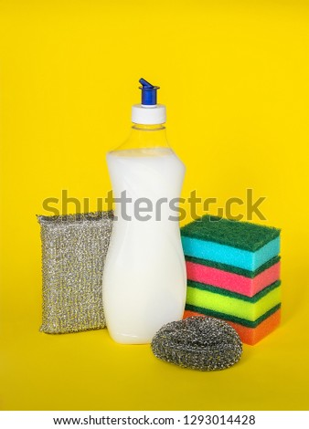 Dishwashing liquid and three types of sponges of different hardness on a yellow background. Kitchen detergent. Household chemicals. Household chores. #1293014428