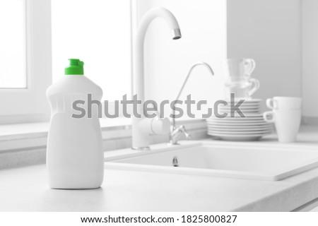 Dishwashing liquid bottle on kitchen sink and clean plates background
