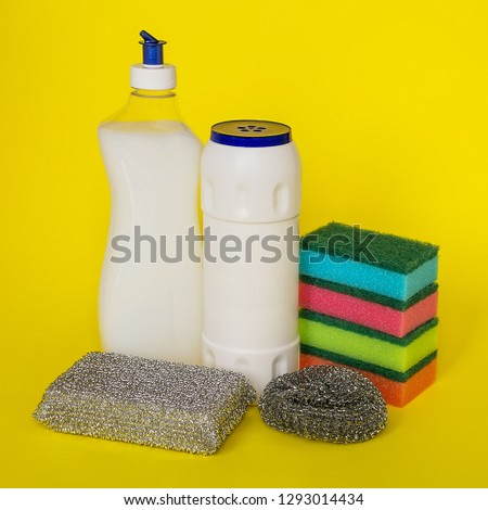 Dishwashing liquid, powder and three types of sponges of different hardness on a yellow background. Kitchen detergent. Household chemicals. Household chores. #1293014434