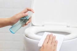 disinfect, sanitize, hygiene care. people using alcohol spray on toilet seat lid and frequently touched area for cleaning and disinfection, prevention of germs spreading during infections of COVID-19