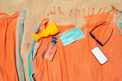 Disinfectant gel, surgery protective mask, suncream, sunglasses and phone on top of towel on sand beach during coronavirus pandemic summer holidays 2020