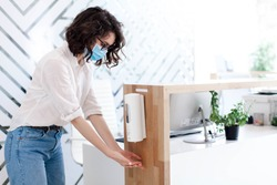 Disinfectant liquid in office. Disinfection hands with sanitizer in public place. Hygiene, staff safety. Protection employees on workplace. Receptionist in mask at reception in hotel during quarantine