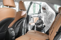 Disinfectant worker character in protective mask and suit sprays bacteria or virus in a car.