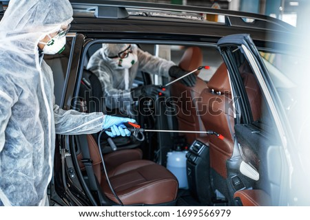 Disinfectant worker in protective masks and suits making disinfection of car seats