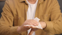 Disinfecting his hands with a wet wipe, the old man thoroughly cleans the inside and outside of his hands, between his fingers, up to his nails. Portrait of disinfecting hands with handkerchief.