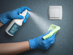 Disinfecting light switch to prevent coronavirus infection. House cleaning during a pandemic.