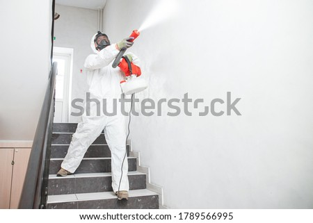 Disinfecting prevent COVID-19, specialist in hazmat suit with disinfect in flight of stairs. Foto stock ©