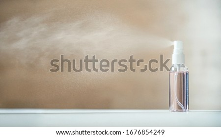 Photo of  Disinfecting sanitizer bottle alcohol spray diffusing antibacterial sanitiser preventing spread of germs, bacterias, viruses on table. Personal hygiene, disinfection, coronavirus protection concept.