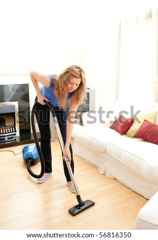 Disintersest woman cleaning a living room with a vacuum cleaner