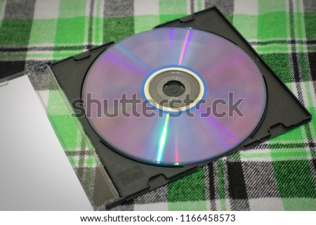 disk. sd-disk. DVD disk. shiny mirror computer disk with box on a plaid green background