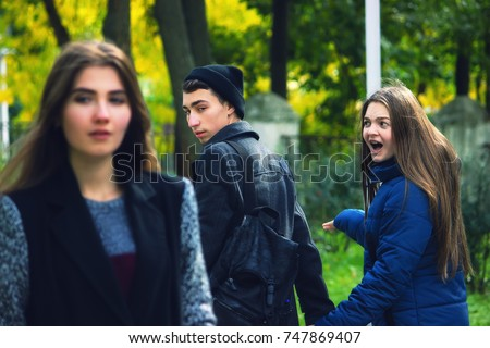 Disloyal man walking with his girlfriend and looking amazed at another seductive girl