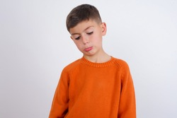 Dismal gloomy rejected Cute Caucasian kid boy wearing knitted sweater against white wall has problems and difficulties, curves lower lip and closes eyes in despair, being in depression