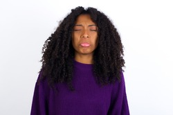 Dismal gloomy rejected Young beautiful African American woman wearing purple knitted sweater against white wall has problems and difficulties, curves lower lip and closes eyes in despair.