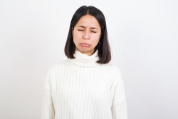 Dismal gloomy rejected Young brunette woman wearing white knitted sweater against white background has problems and difficulties, curves lower lip and closes eyes in despair, being in depression