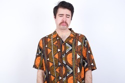 Dismal gloomy rejected Young caucasian man wearing generic pattern printed shirt against yellow wall has problems and difficulties, curves lower lip and closes eyes in despair, being in depression