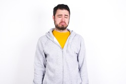 Dismal gloomy rejected Young caucasian man wearing tracksuit over white background has problems and difficulties, curves lower lip and closes eyes in despair, being in depression