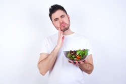 Dismal gloomy rejected Young handsome Caucasian man holding a salad bowl against white background has problems and difficulties, curves lower lip and closes eyes in despair, being in depression
