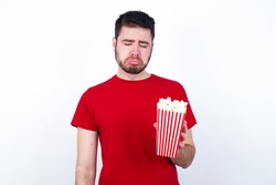 Dismal gloomy rejected Young handsome man in red T-shirt against white background eating popcorn has problems and difficulties, curves lower lip and closes eyes in despair, being in depression