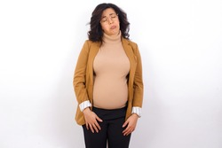 Dismal gloomy rejected young pregnant businesswoman wearing beige blazer over white background has problems and difficulties, curves lower lip and closes eyes in despair, being in depression
