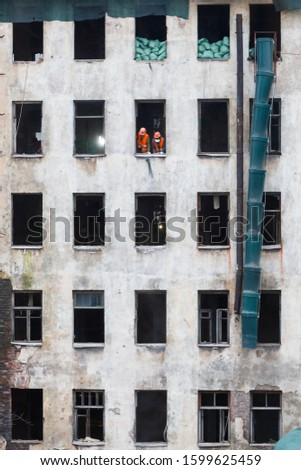Dismantling or reconstruction with a complete replacement of all communications inside of the old house, construction workers in orange vests and hardhat standing by the window. Construction site.