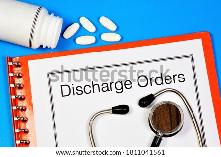Photo of  Dismissal orders - text inscription on a medical folder of documents, against the background of a stethoscope and medicinal tablets.