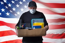 Dismissed American in a medical mask. Unemployed on background of USA flag. Concept - man became unemployed due to Covid-19. Unemployment due to coronavirus. Unemployment USA. Sad man holding a box