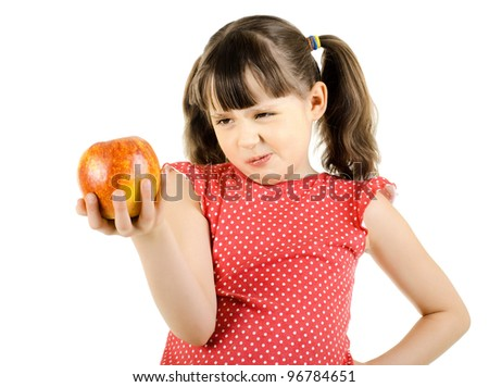 disobedient little girl hold apple and make displeased  grimace, on white background, isolated