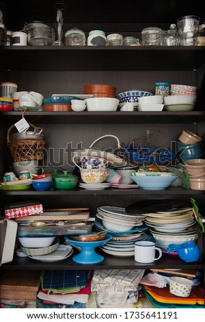 Disorganised kitchen cupboard with stacks of mismatched ceramic plates and bowls, piles of mugs and glasses and lots of jars and vases randomly shoved onto the shelves Foto stock ©