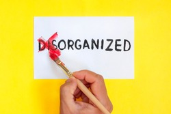disorganized is organized concept. Hand with brush. corrected word disorganized on yellow background.