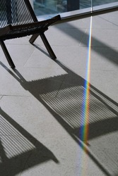 Dispersing sunlight from the glass splitting into a spectrum on a floor. Light and shadow from the chair. Decomposition of light into a color spectrum. Shallow depth of field
