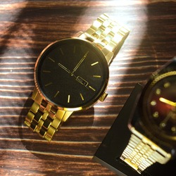 Display accessories gold watch shiny luxury with sunlight on dark wood background depth close up
