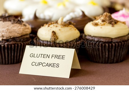 Display of assorted gluten free cupcakes sitting on display table