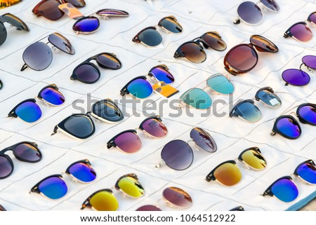 Display of colorful sunglasses for sale in a street #1064512922