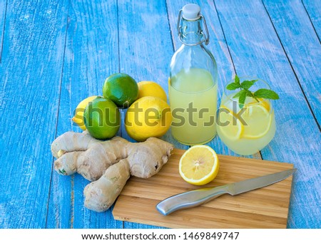 Display of freshly homemade Lemon-, Lime- and Ginger-Lemonade with fresh lemons, limes and ginger, cutting board, knife, glass and vintage latch top bottle