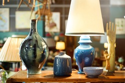 Display of handmade colorful glazed pottery or ceramics in a store with a table lamp, vases, bowl, hands on stands and jar in a shop interior