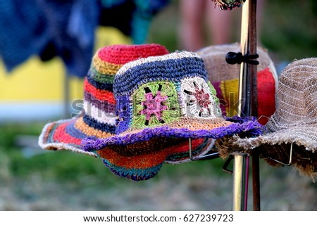 Display of  multicolored hats made from hemp and straw, with stripes and flower designs displayed on a  hat stand at an outdoor festival market stall #627239723