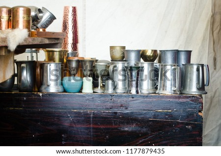 Display of vintage pewter and copper goblets, chalices and tankards on a wooden chest at a ren renaissance faire tent. #1177879435