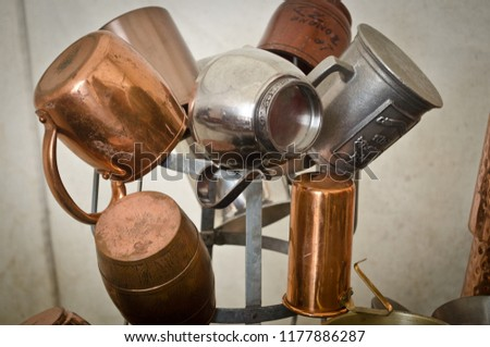 Display tree of pewter silver and copper cups tankards with a rustic white canvas background. #1177886287