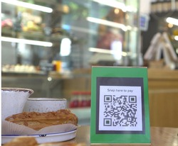 Display with qr code on the table in the restaurant. Contactless payment. A man scans the QR code displayed by the merchant with their phone to pay for service