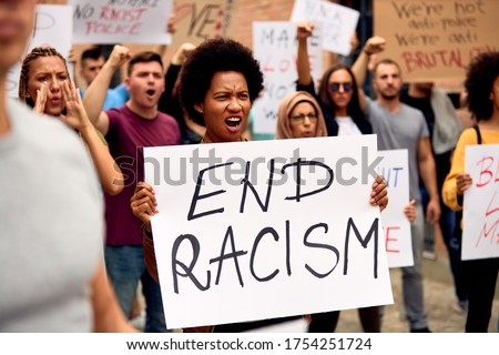 Displeased African American woman holding end racism placard while protesting with crowd of people on city streets.
