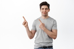 Displeased and skeptical adult man frowning and looking judgemental, pointing fingers left and staring with doubtful face, standing over white background