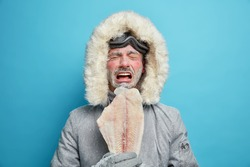 Displeased arctic person covered with frost during severe cold day freezing climate and weather holds frozen fish lives in northern parts. Male eskimos in outerwear poses against blue background