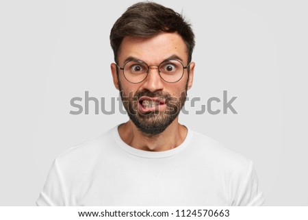 Displeased bearded male frowns face with displeasure, has irritated expression, raises eyebrows and clenches teeth, being discontent, argues with enemy, wears spectacles. Negative facial expressions