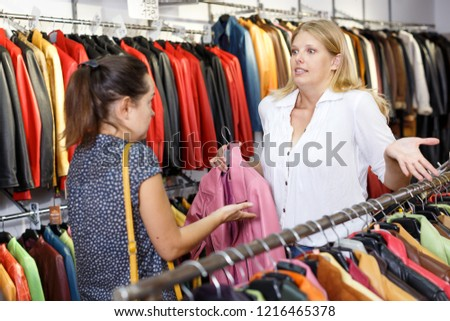 Displeased customer in leather clothes shop talking with salesgirl