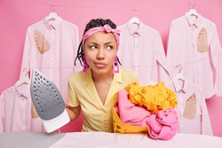 Displeased dark skinned pensive housemaid looks thoughtfully away holds stack on unfolded laundry and steam electic iron going to stroke linen wears headband casual dress works in wash house