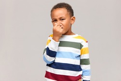 Displeased dark skinned 8 year old boy grimacing and pinching nose because of disgusting smell. Disgusted child can't stand intolerable stink, holding breath. Body odor and dirty socks concept