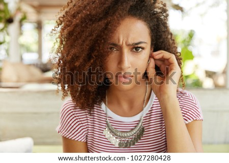 Displeased dark skinned young female doesn`t want to be photographed, looks with gloomy and unhappy expression into camera, being offended or abused by someone. Discontent African American woman