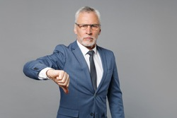 Displeased elderly gray-haired mustache bearded business man in classic blue suit shirt tie isolated on grey background studio portrait. Achievement career wealth business concept. Showing thumb down