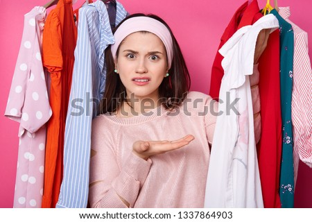 Displeased female shows white shirt, being dissatisfied with size. Girl stands at clothes on hangers in wardrobe. Discontent lady wants same blouse in diferent colour. Shopping and fasion concept.